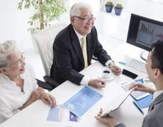 Sales person and old couple are simulating real estate investmen